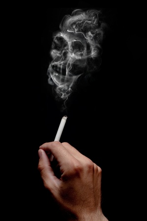 A smoking cigarette over a dark background, low key light. photo