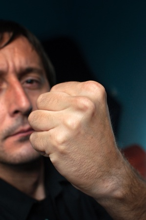 enrage: Caucasian male with a fist, close up image.