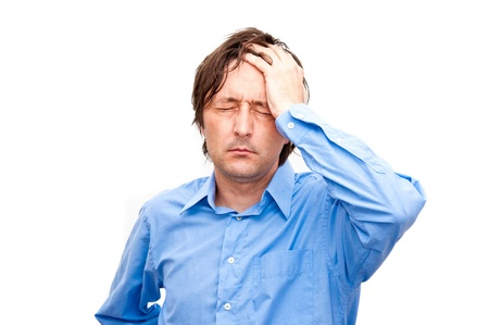 Young businessman looking anxious and worried, having a headache photo