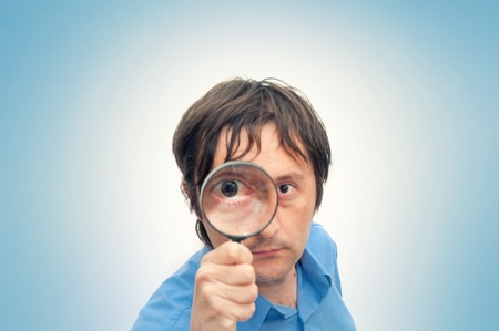 Young man with magnifying glass photo