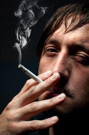 man smoking: Man smoking cigarette over black background, low key light image