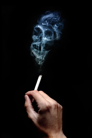 cigarette lighter: A smoking cigarette over a dark background, low key light. Stock Photo