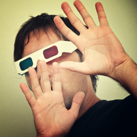 scarry: Man with anaglyph 3D glasses making funny face with his hands up. Stock Photo