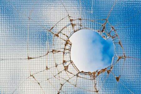 Broken glass - cracked with hole over blue sky. photo