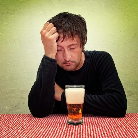 ubriaco: Uomo ubriaco al tavolo con un bicchiere di birra fredda, luce pub.
