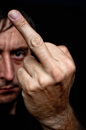 animal finger: Man showing a middle finger, low key portrait Stock Photo