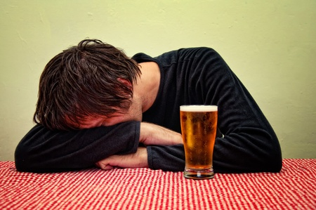 drunk man: Drunk man at the pub table with a glass of cold, light beer.