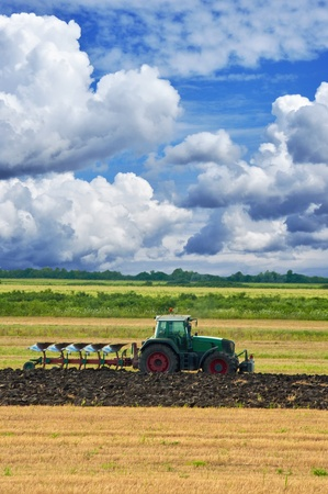 Agriculture tractor in yellow field outdoors in summer with plough photo