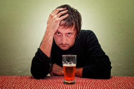 alcoholic man: Drunk man at the pub table with a glass of cold, light beer.
