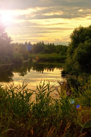 Quiet summer pond in the dusk with subtle lens flare caught with the camera. Stock Photo - 10148531