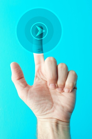 Male hand is pressing a Play touchscreen button