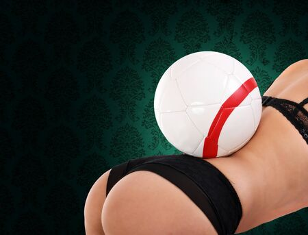 ass fun: sexy young woman closeup with soccer ball on her back Stock Photo