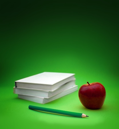 School books with apple on desk photo