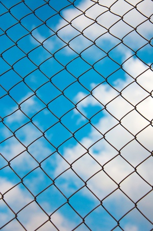 Chain link wired grid fence pattern against blue sky. Stock Photo