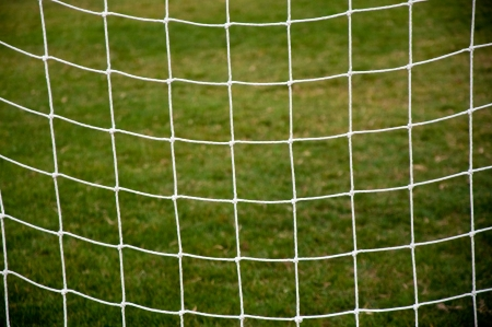 Soccer goal net against green background photo