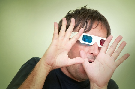 Man with anaglyph 3D glasses making funny face with his hands up. Stock Photo - 10666088