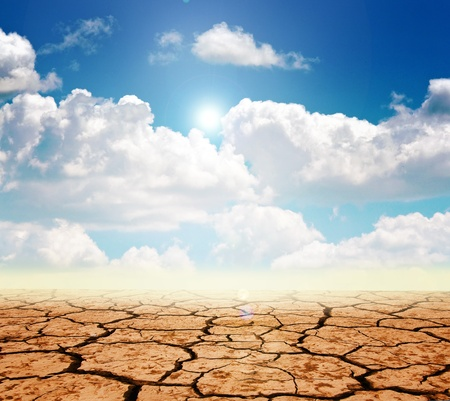 arid: Drought land against a blue sky with clouds