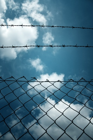 razor wire: Barbed wire fence against a blue sky with clouds