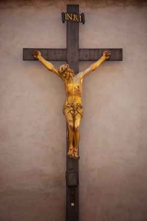 A statue of Jesus Christ crucified against concrete wall photo