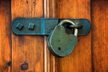 Closed wooden door with metal lock photo