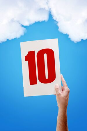 White paper with number ten in male hand on blue sky background photo