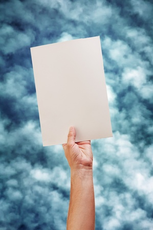 Hand and paper, against the sky with the clouds as a background. Stock Photo - 10954356