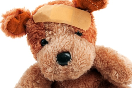 molest: Cute little teddy bear with plaster on his head over a white background