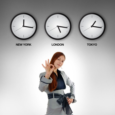 Young and beautiful business woman with clocks showing time in different time zones. photo
