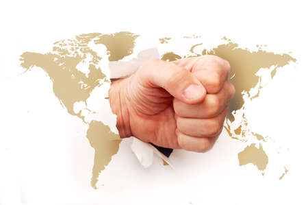 worl: Fist ripping the paper with the worl map printed on it. Stock Photo