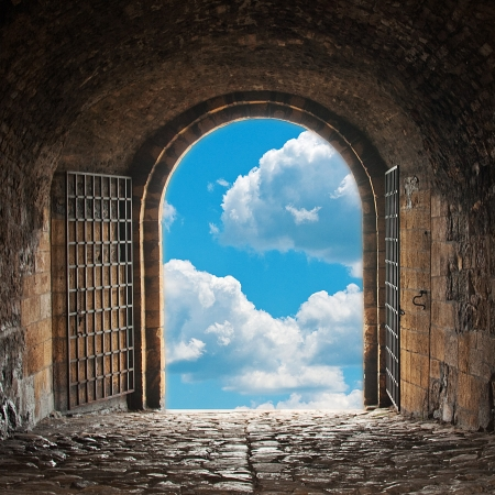 heavens gates: A dark corridor with a arch opening to a beautiful cloudy sky