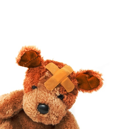 stuffed toy: Cute little teddy bear with plaster on his head over a white background