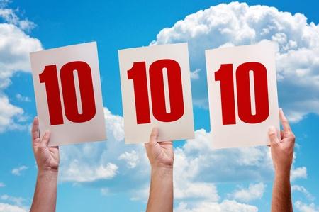 numero diez: Papel blanco con el número diez en manos de los hombres sobre fondo de cielo azul Foto de archivo