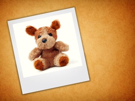 stuffed toy: Cute little bear toy in a picture frame over a grunge background Stock Photo