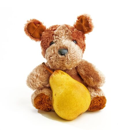 stuffed toy: Cute little bear toy holding a pear over a white background Stock Photo