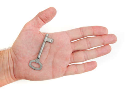 Male hand holding a key to the house, image is taken over a white background. Stock Photo - 11596942