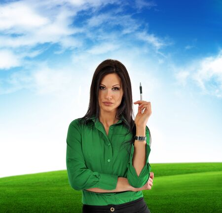green computing: Beautiful nusinesswoman in green shirt, outdoor portrait. Clouds in the background.