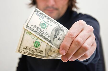Casual adult man is paying in dollar bills, corruption and bribe concept. Stock Photo - 11597027