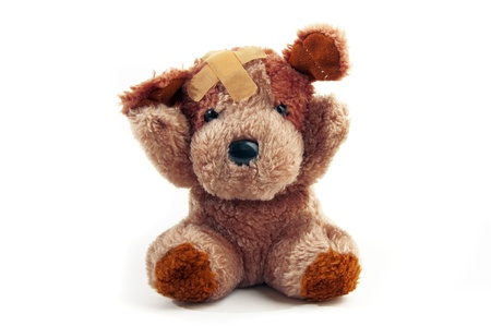 molest: Cute little bear toy with plaster on his head over a white background Stock Photo