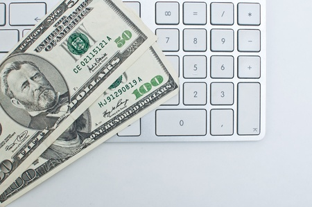financial item: Office desktop, a computer keyboard and couple of dollar bills. Stock Photo