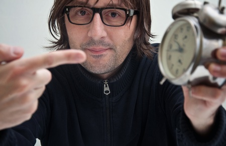 Man showing at the clock with his index finger, indicating that it is too late. Stock Photo - 11597055