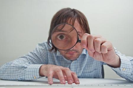 enlarged: Divertente l'immagine di un uomo d'affari con una lente d'ingrandimento, un occhio � allargata.