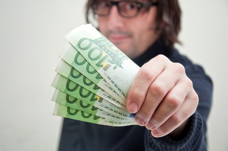 Casual adult man is paying in euros, corruption and bribe concept. photo