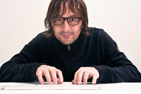 Man with a funny face is typing on computer keyboard Stock Photo - 11597066