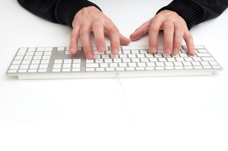 Man is typing on computer keyboard on a white desktop photo