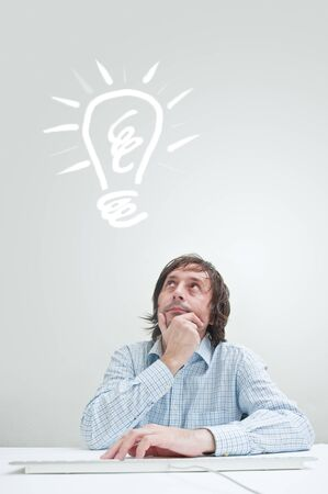 Businessman with an idea, drawn light bulb above his head photo