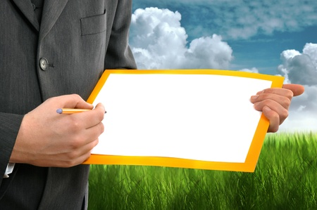 Businessman writing on the blank paper left for copyspace. Green grass and cloudy sky in the background as environmental concept. photo