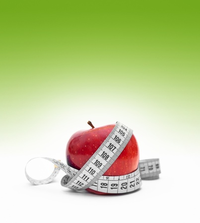 Fresh red tasty apple with measuring tape, fitness concept. photo