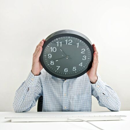 Desperate businessman with a clock instead of his head, looking desperately down as the time passes by.  photo