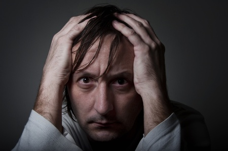 Very depressive man in white shirt holding head with his hands in a low light atmospere. Stock Photo - 11929189