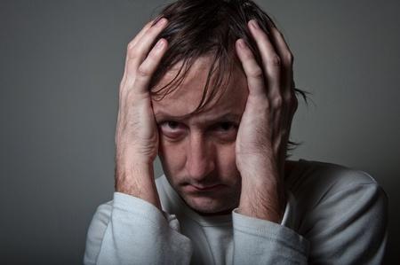 desperate: Muy depresivo hombre de camisa blanca sosteniendo la cabeza con las manos en un atmospere con poca luz.